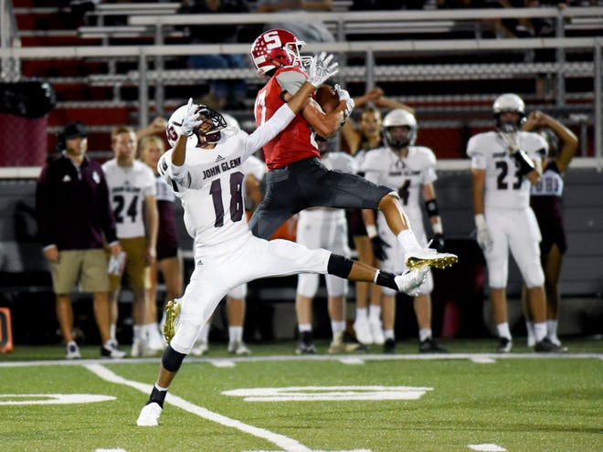 Sheridan's Jacob Rhodes makes a leaping interception in front of John Glenn's Joseph Clifford during the Generals' 37-7 win on Friday night at Paul Culver Jr. Stadium. Rhodes also caught a pair of touchdown passes as Sheridan improved to 3-0.
