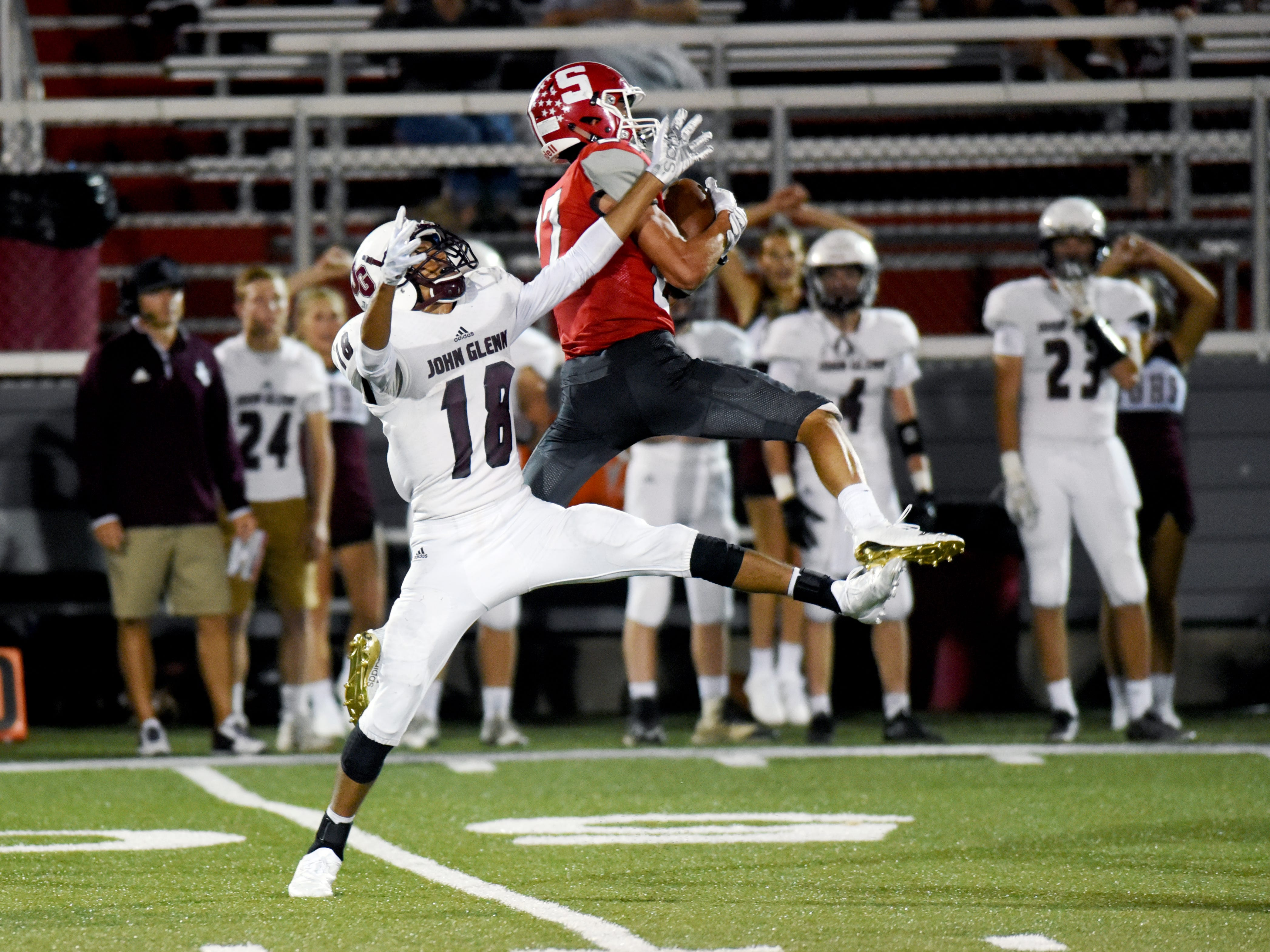 Sheridan's Jacob Rhodes makes a leaping interception in front of John Glenn's Justin Clifford during the Generals' 37-7 win on Friday night at Paul Culver Jr. Stadium. Rhodes also caught a pair of touchdown passes as Sheridan improved to 3-0.