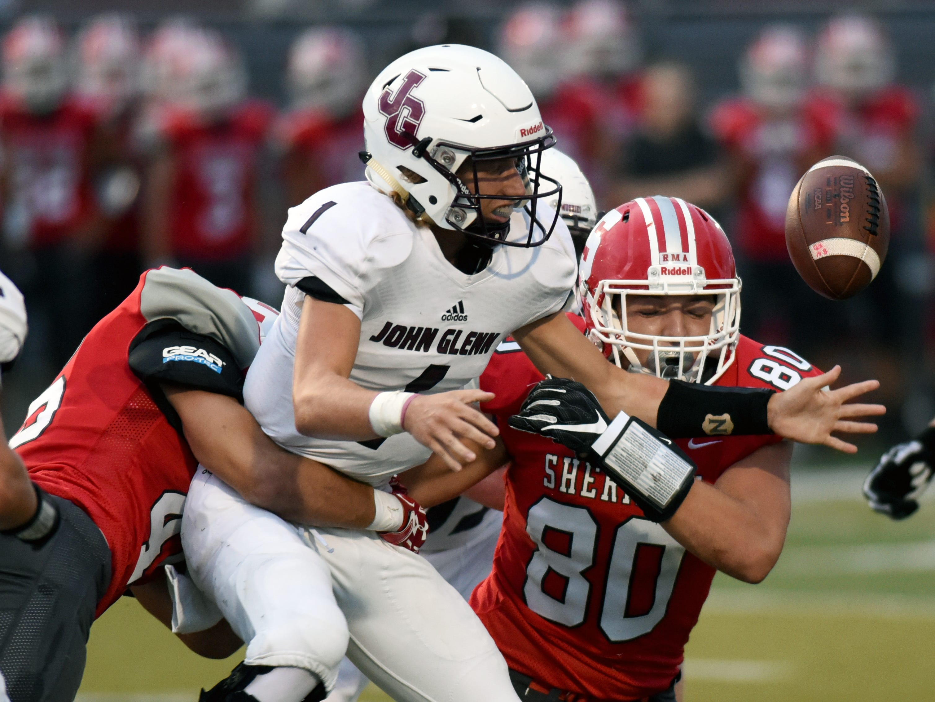 Evan Williams loses the ball after being sacked by Sheridan's Chance King, left, and Adam Boyle. Sheridan won, 37-7, on Friday night at Paul Culver Jr. Stadium.