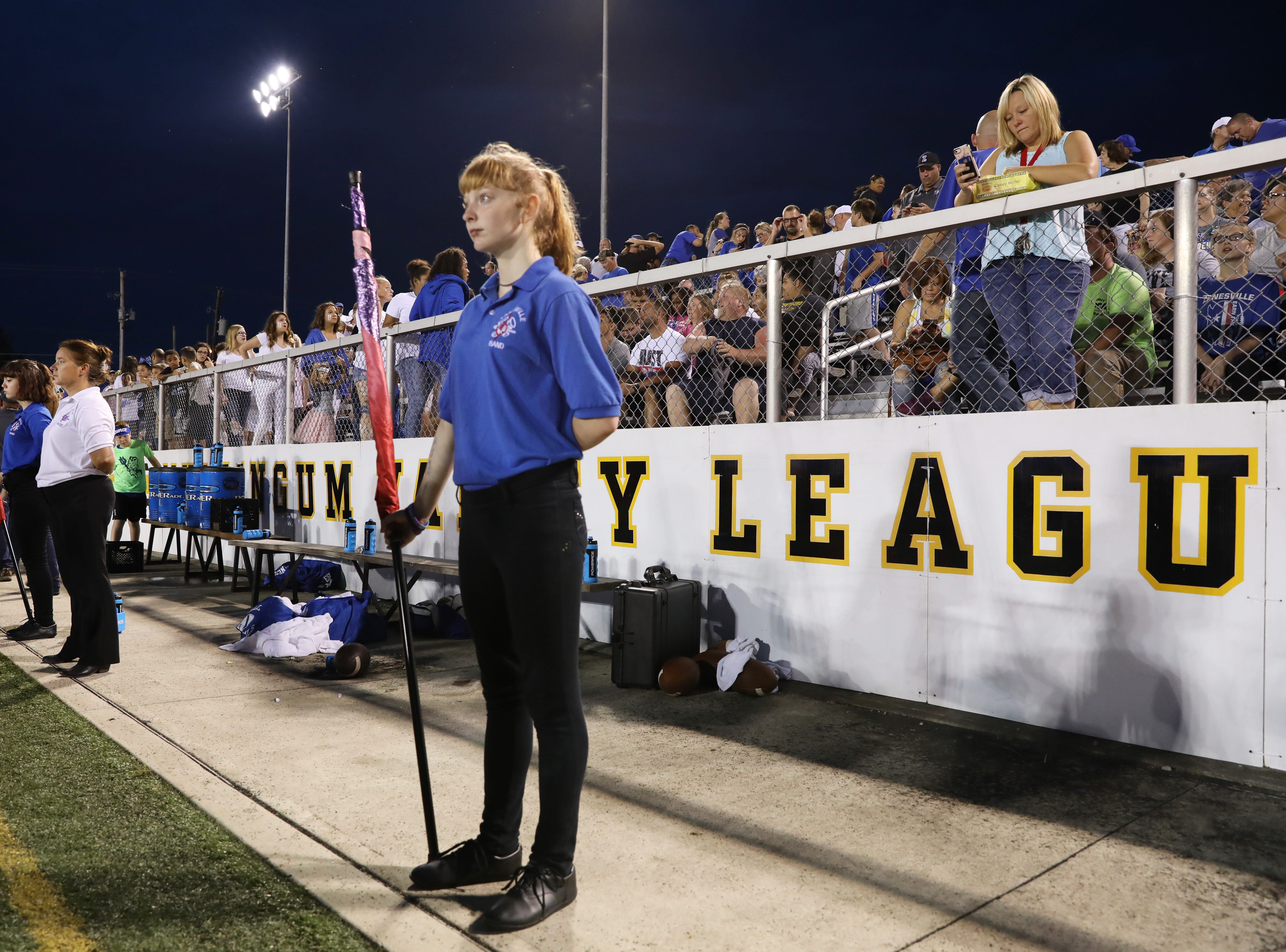 A member of the Zanesville flag corps waits to take the field for halftime against Tri-Valley.