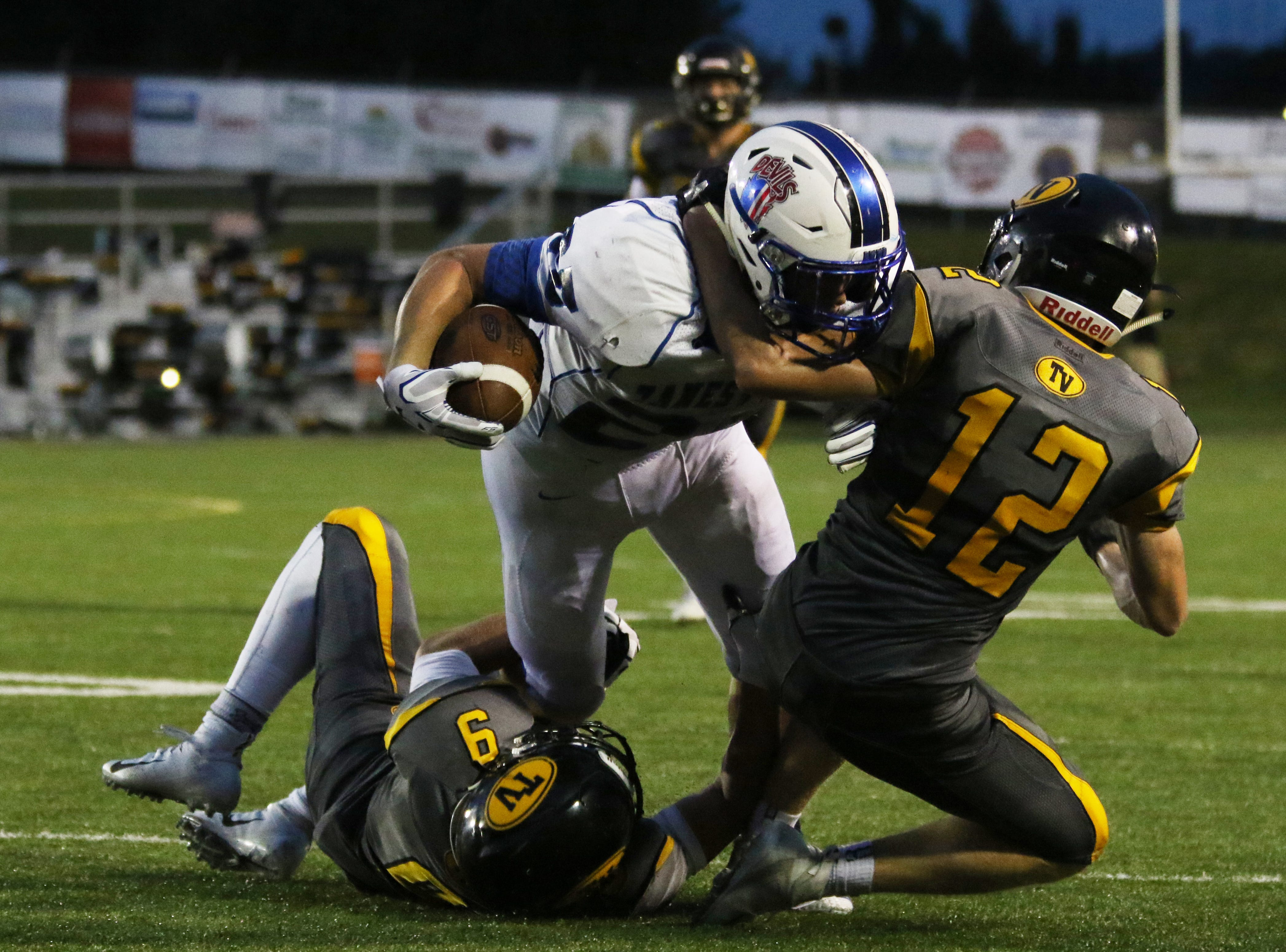 Tri-Valley's Graham Cameron (12) and Sam Slaboden tackle Zanesville's Dkker Davis.