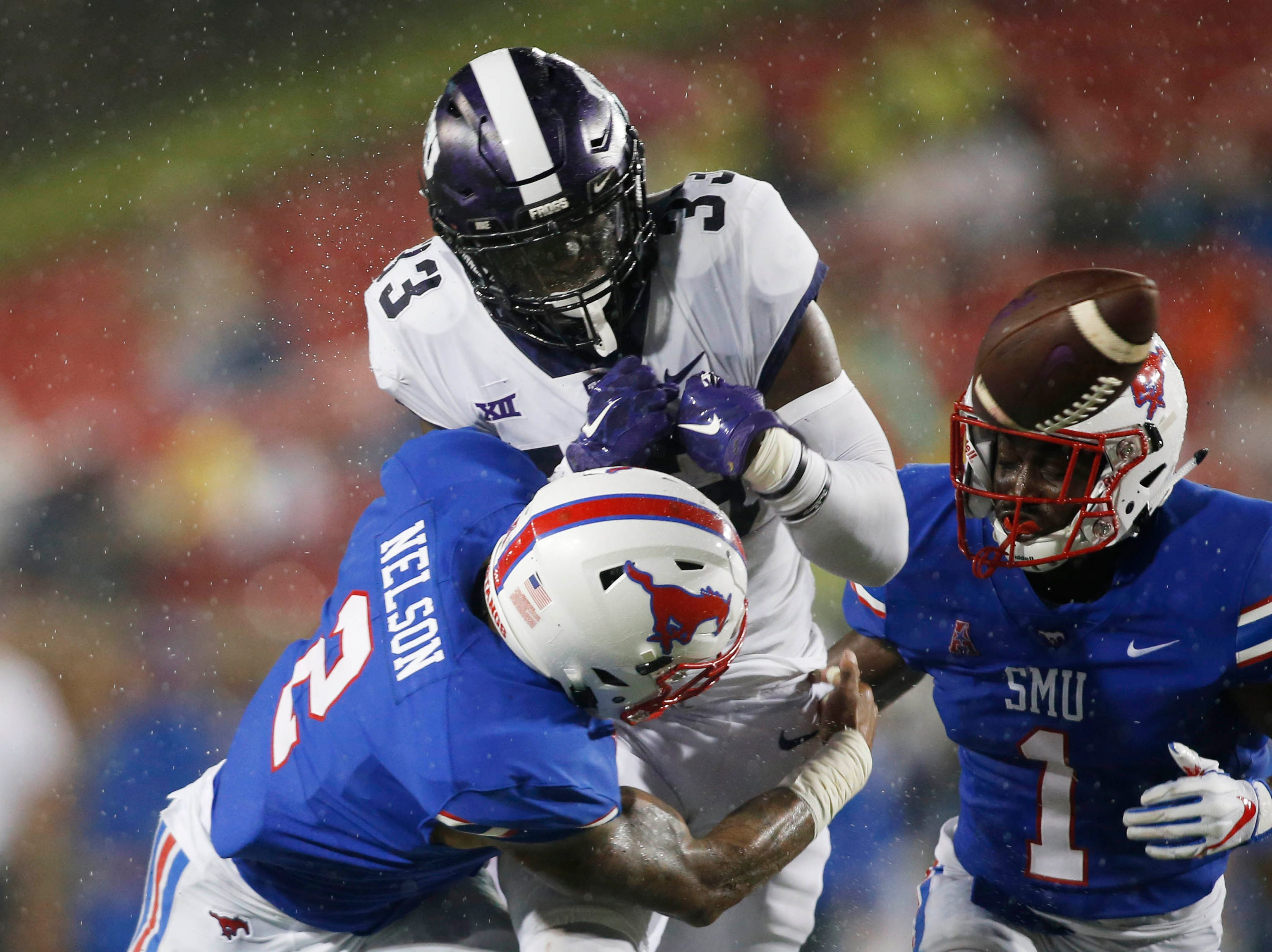 TCU Horned Frogs running back Sewo Olonilua (33) is tackled by Southern Methodist Mustangs safety Patrick Nelson (2) and fumbles the ball in the second quarter at Gerald J. Ford Stadium.