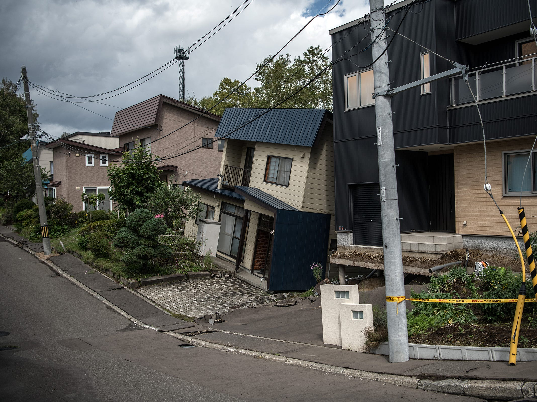 A house leans over following the partial collapse of the ground around it after an earthquake, on Saturday, in Kiyota, Japan.