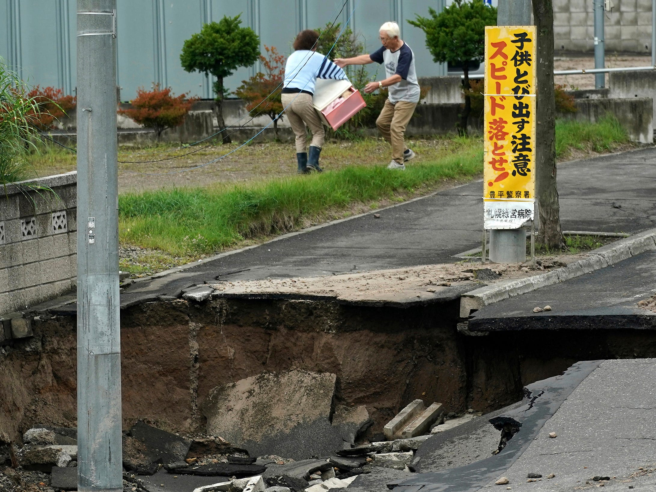 Residents bring out their belongings from an earthquake-damaged house in Kiyota ward of Sapporo, Hokkaido, northern Japan, Saturday.  Some parts of the city were severely damaged, with houses atilt and roads crumbled or sunken. A mudslide left several cars half buried, and the ground subsided in some areas, leaving drainpipes and manhole covers protruding by more than a meter (yard) in some places.