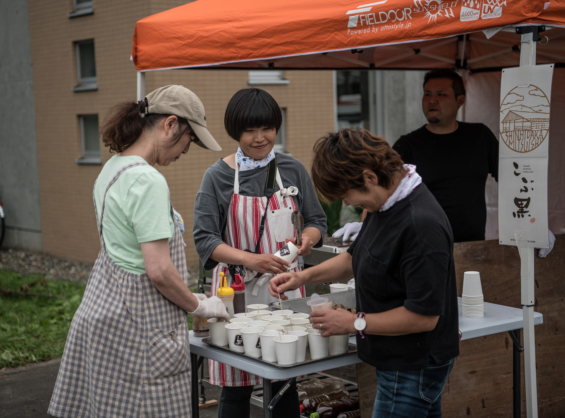 A volunteer provides food and drinks, Saturday, to people affected by an earthquake, in Atsuma, Japan.