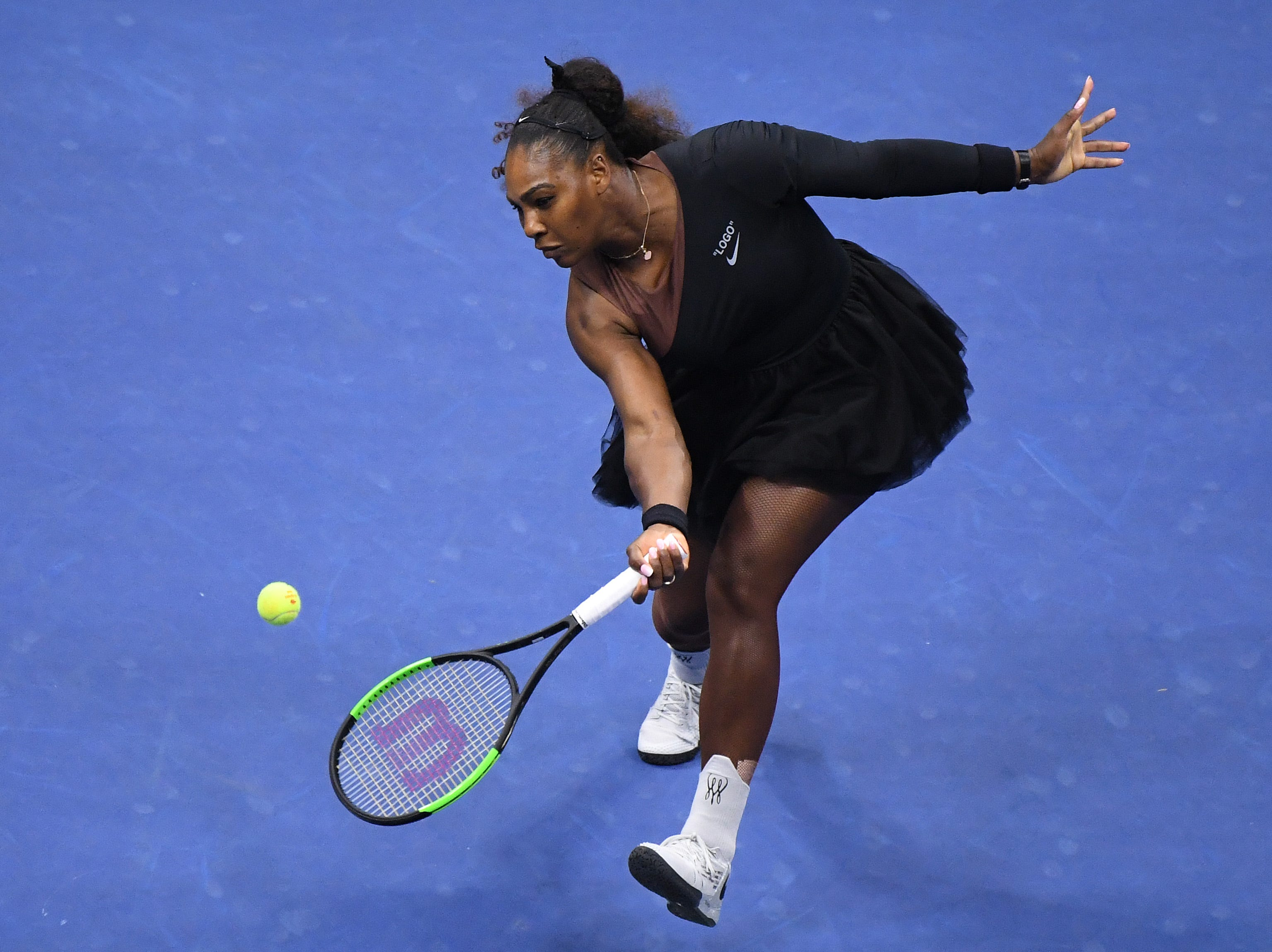Serena Williams hits a volley against Naomi Osaka.