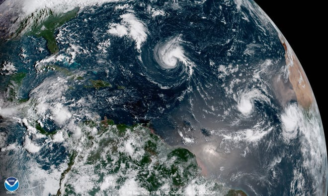 Florence, the swirl of clouds at the center of this satellite image from early Saturday, Sept. 8, 2018, continues to slowly move toward the U.S. East Coast. Two other tropical systems are also spinning in the central and eastern Atlantic (right.)