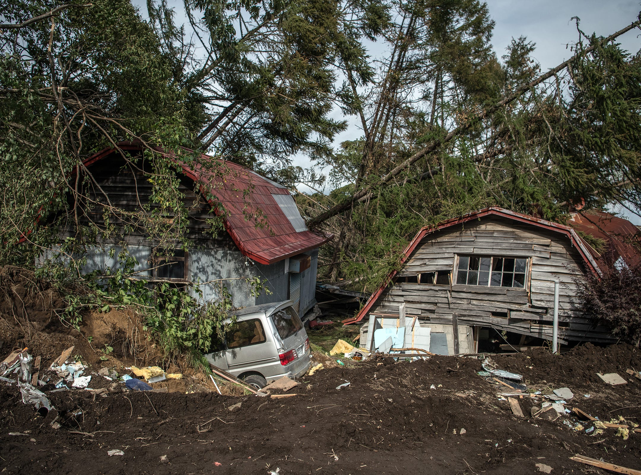 A crushed car and buildings lie partially submerged in mud after being struck by a landslide triggered by an earthquake, on  in Atsuma, Japan.
