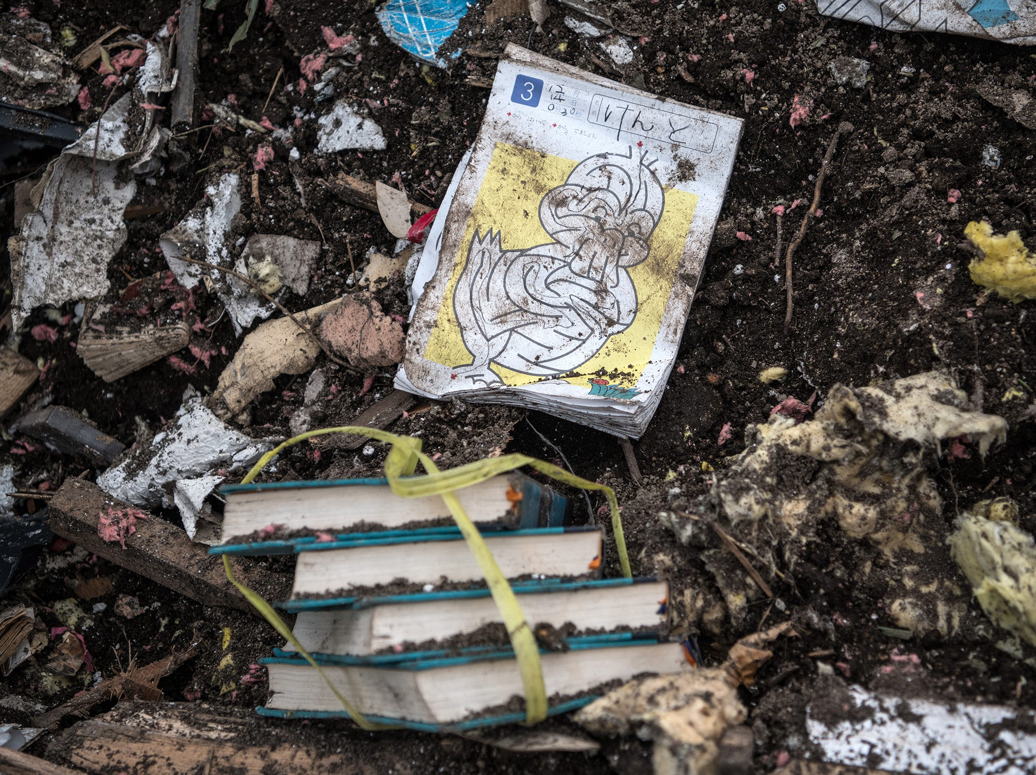 A children's book lies on the ground amongst the rubble of a building destroyed by a landslide triggered by an earthquake, Saturday, in Atsuma, Japan.