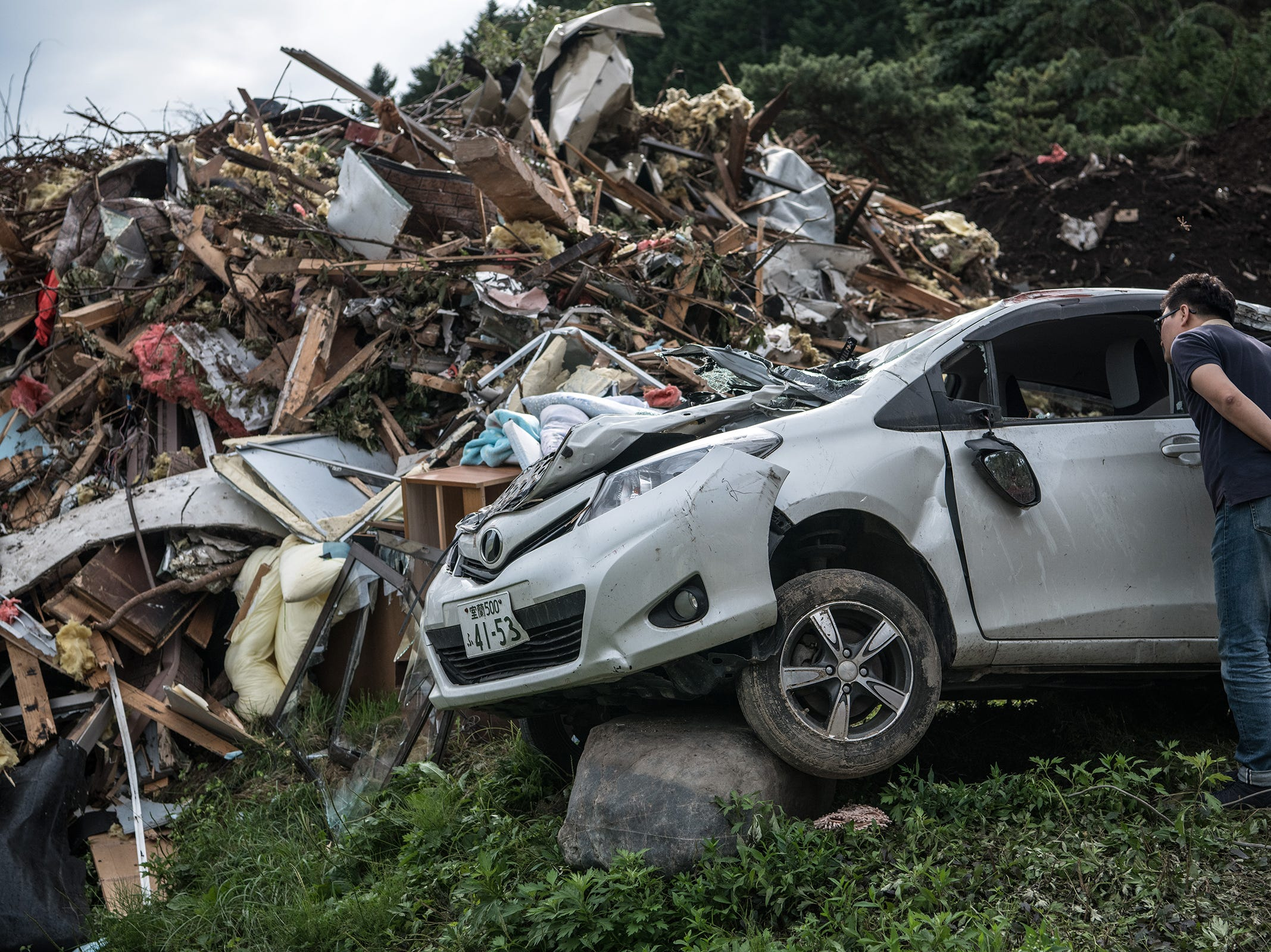 A man peers inside a destroyed car next to the ruins of a house that was struck by a landslide triggered by an earthquake, on Sept. 8, 2018, in Atsuma near Sapporo, Japan. Twenty one people are now confirmed to have been killed with eight still missing and hundreds injured two days after a powerful 6.7-magnitude earthquake struck the northern Japanese island of Hokkaido.