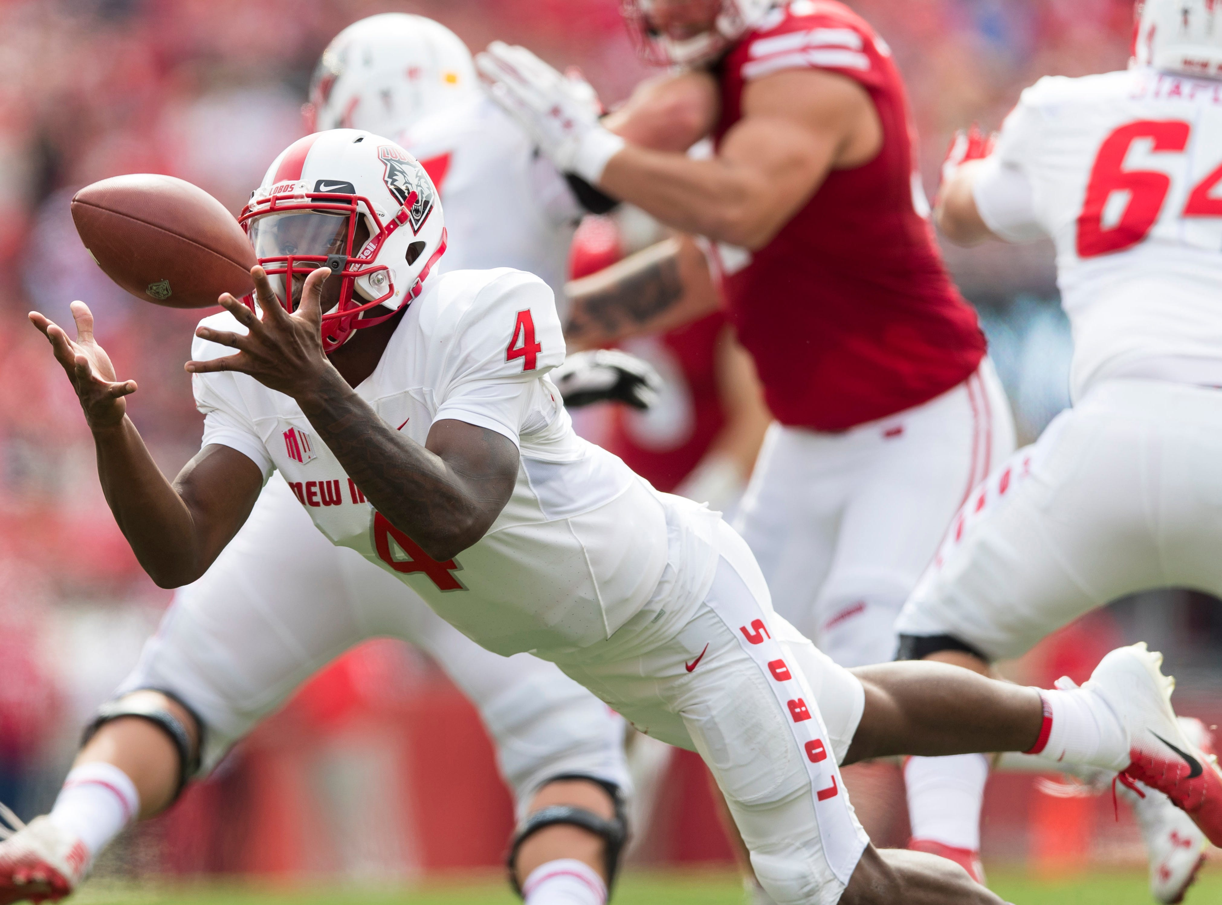 New Mexico Lobos quarterback Sheriron Jones (4) dives to catch the snap during the second quarter against the Wisconsin Badgers at Camp Randall