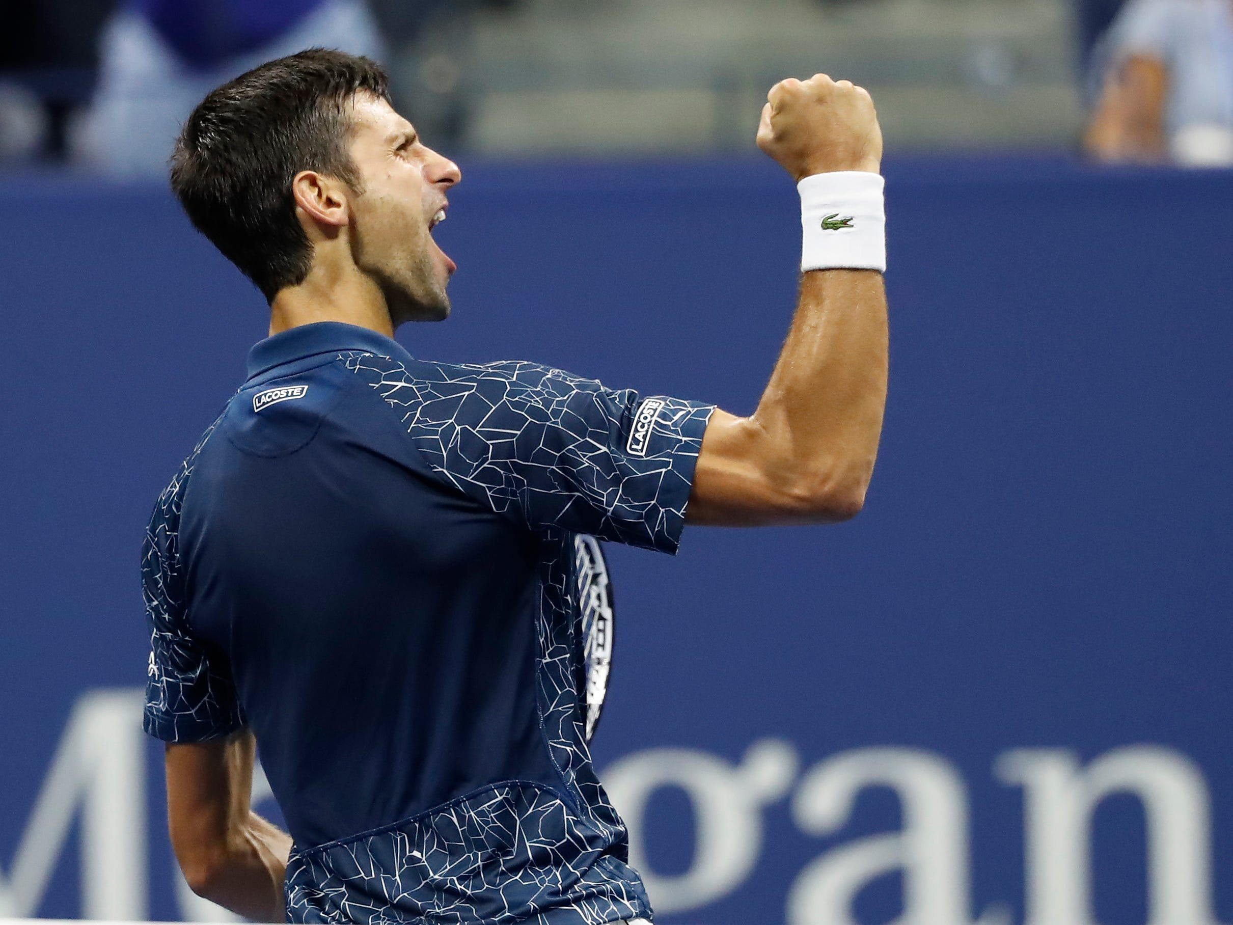 Novak Djokovic pumps his first after beating Kei Nishikori in the US Open semifinal.