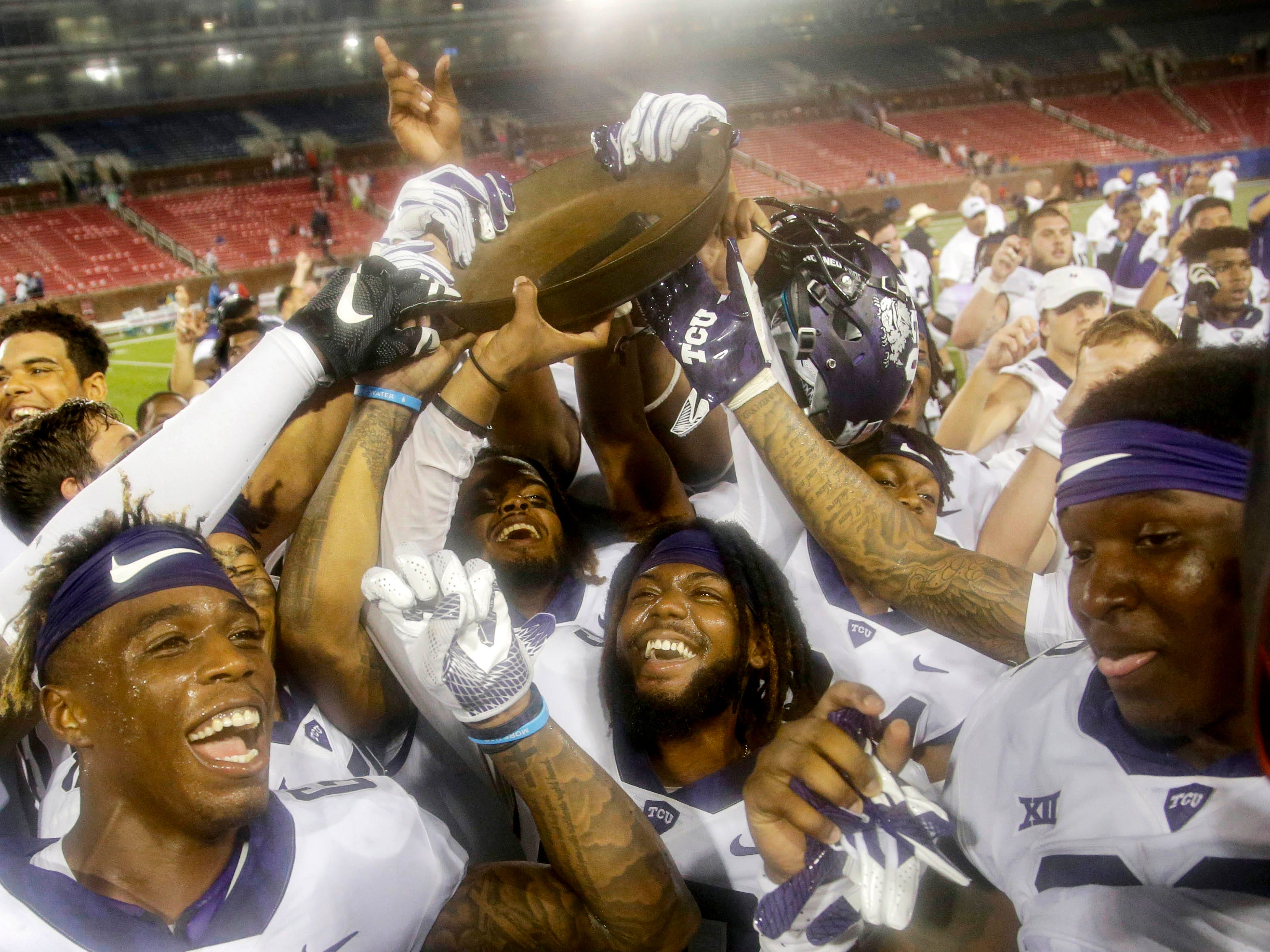 TCU Horned Frogs players hold up the Iron Skillet after the game against the Southern Methodist Mustangs.