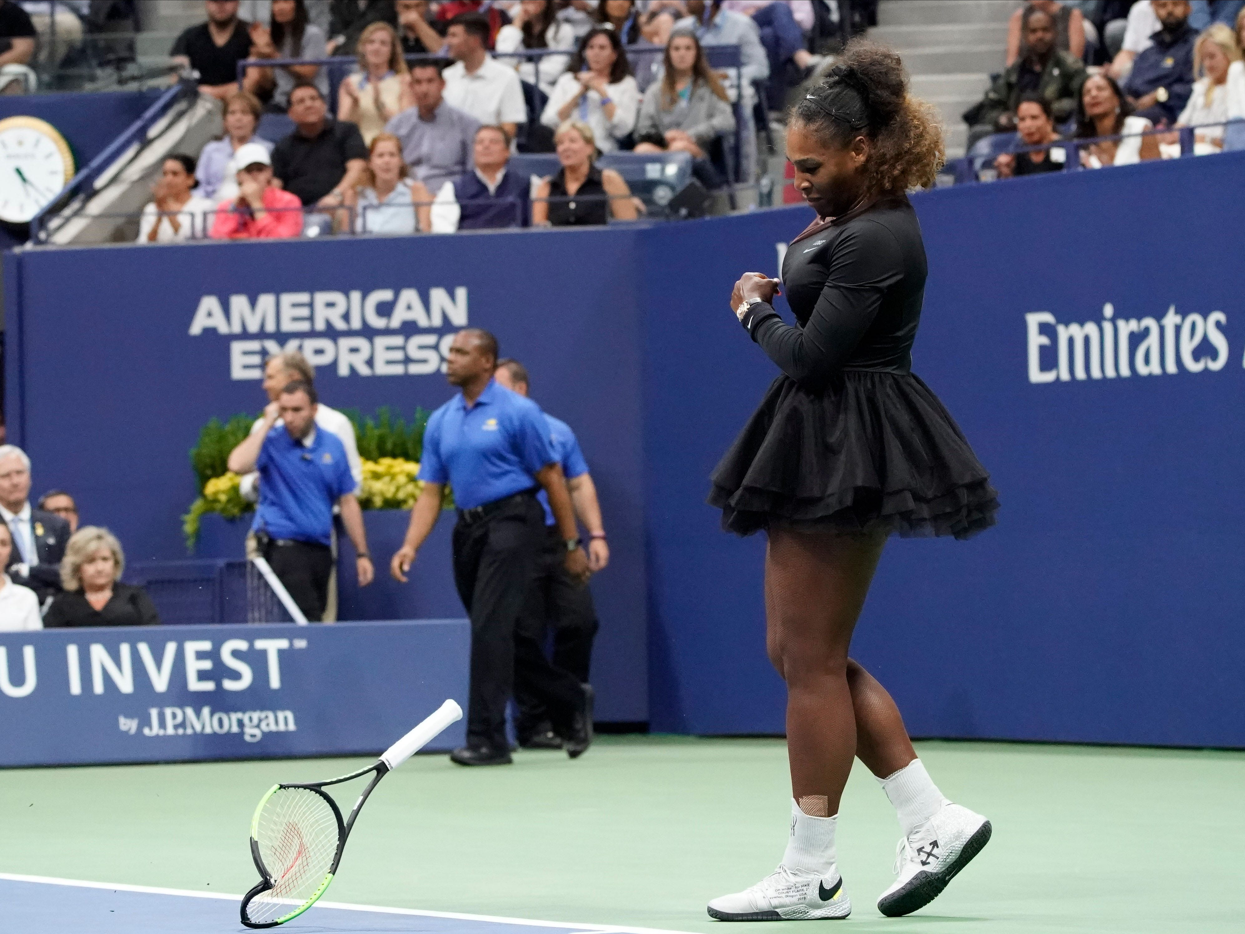Serena Williams breaks her racket after losing a game to Naomi Osaka. Williams lost a point for a code violation.