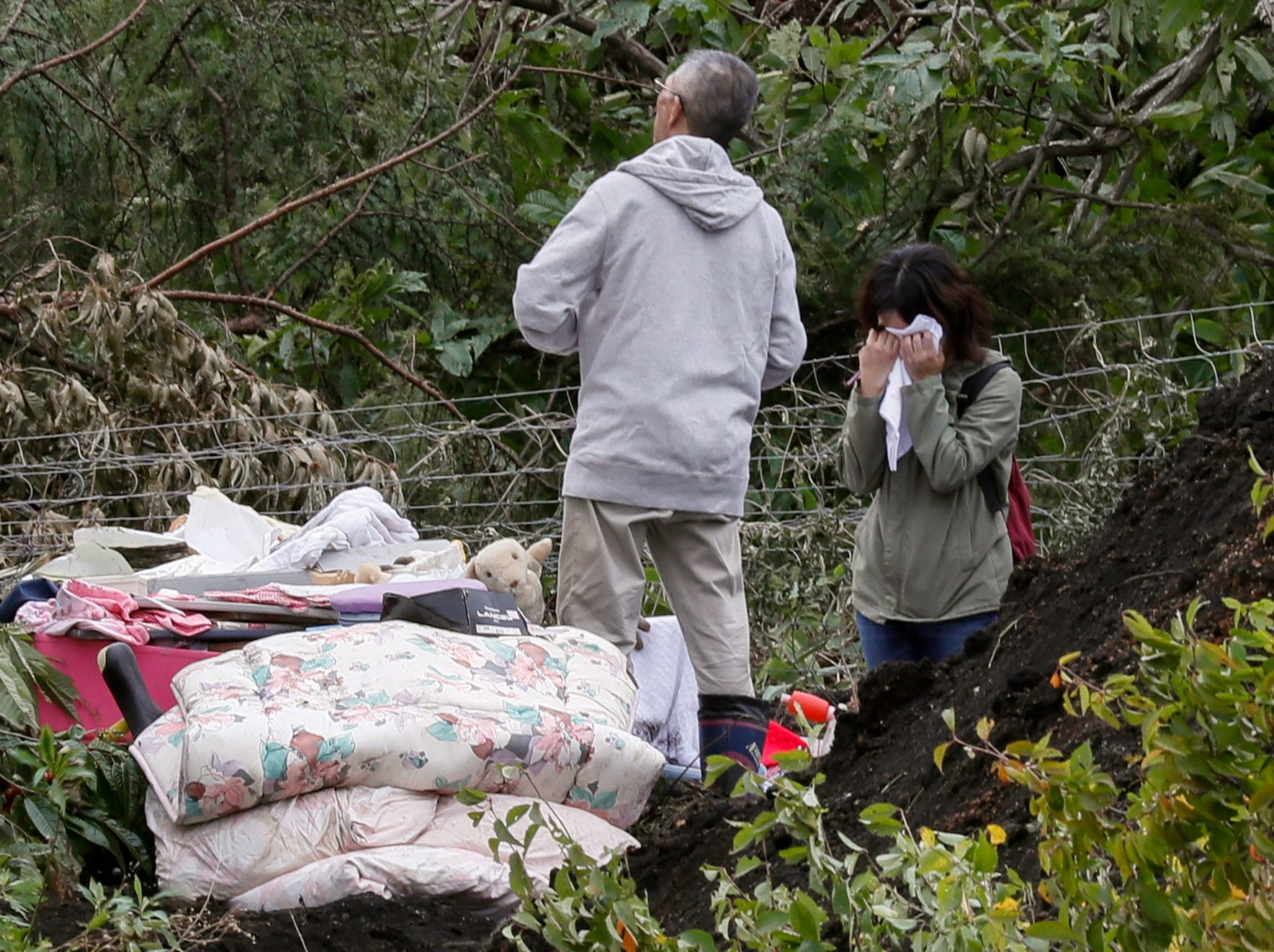 Family members react at a large landslide site in the Yoshino district of Atsuma, an area that was hit by a powerful earthquake, in Hokkaido, Japan. A 6.7 magnitude earthquake killed at least 20 people, injurying many, media reported.