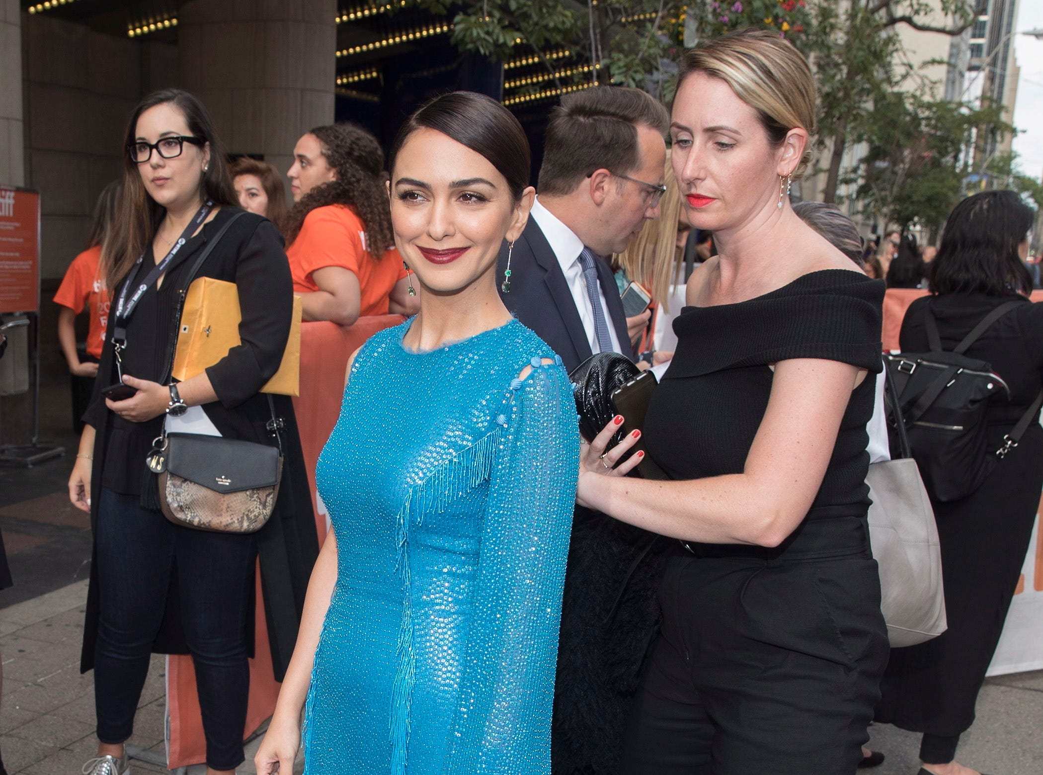 "Nazanin Boniadi, in blue, prepares to walk the red carpet at the premiere of her new film, ""Hotel Mumbai,"" on Friday."