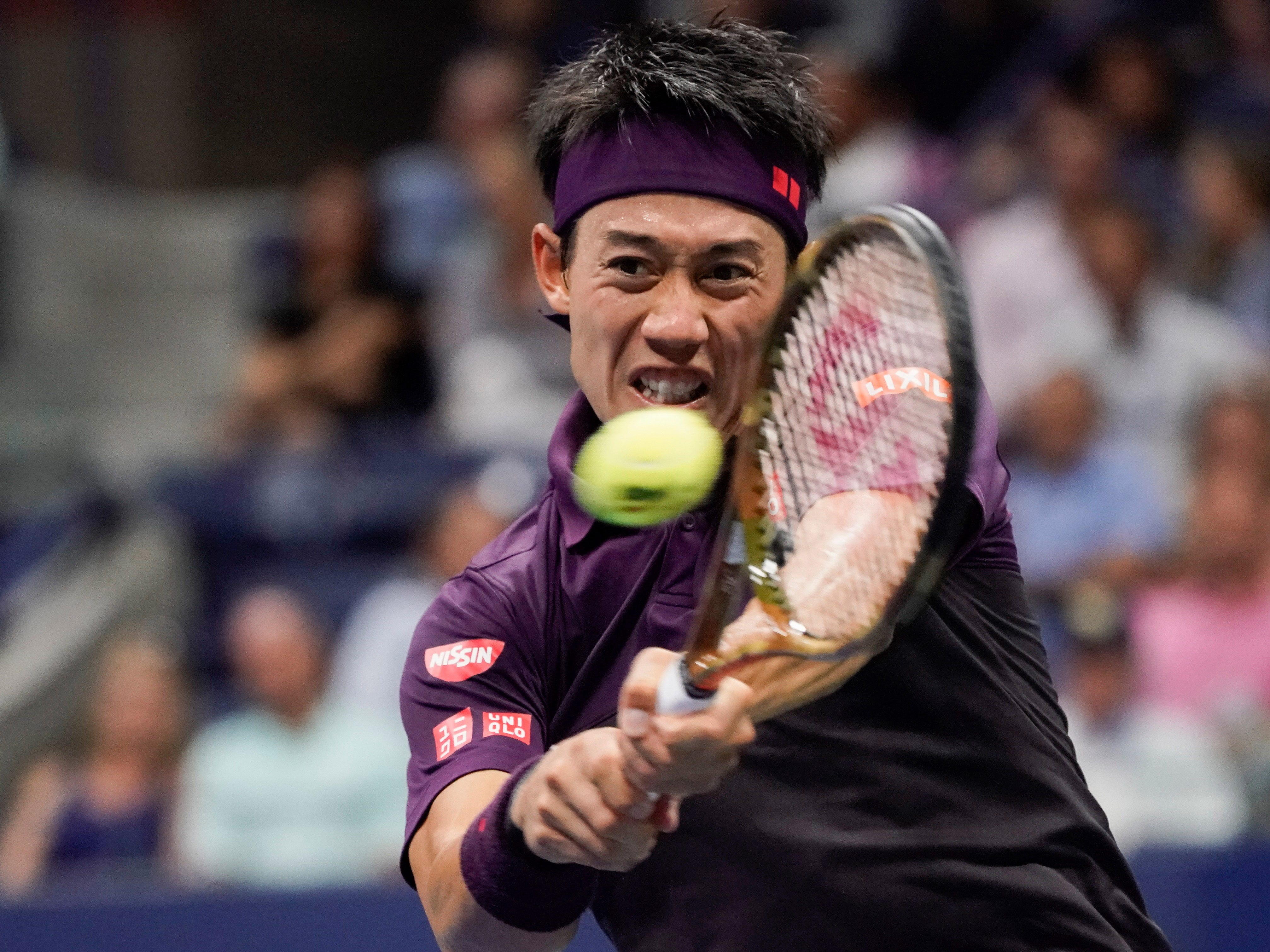 Kei Nishikori of Japan hits to Novak Djokovic of Serbia.