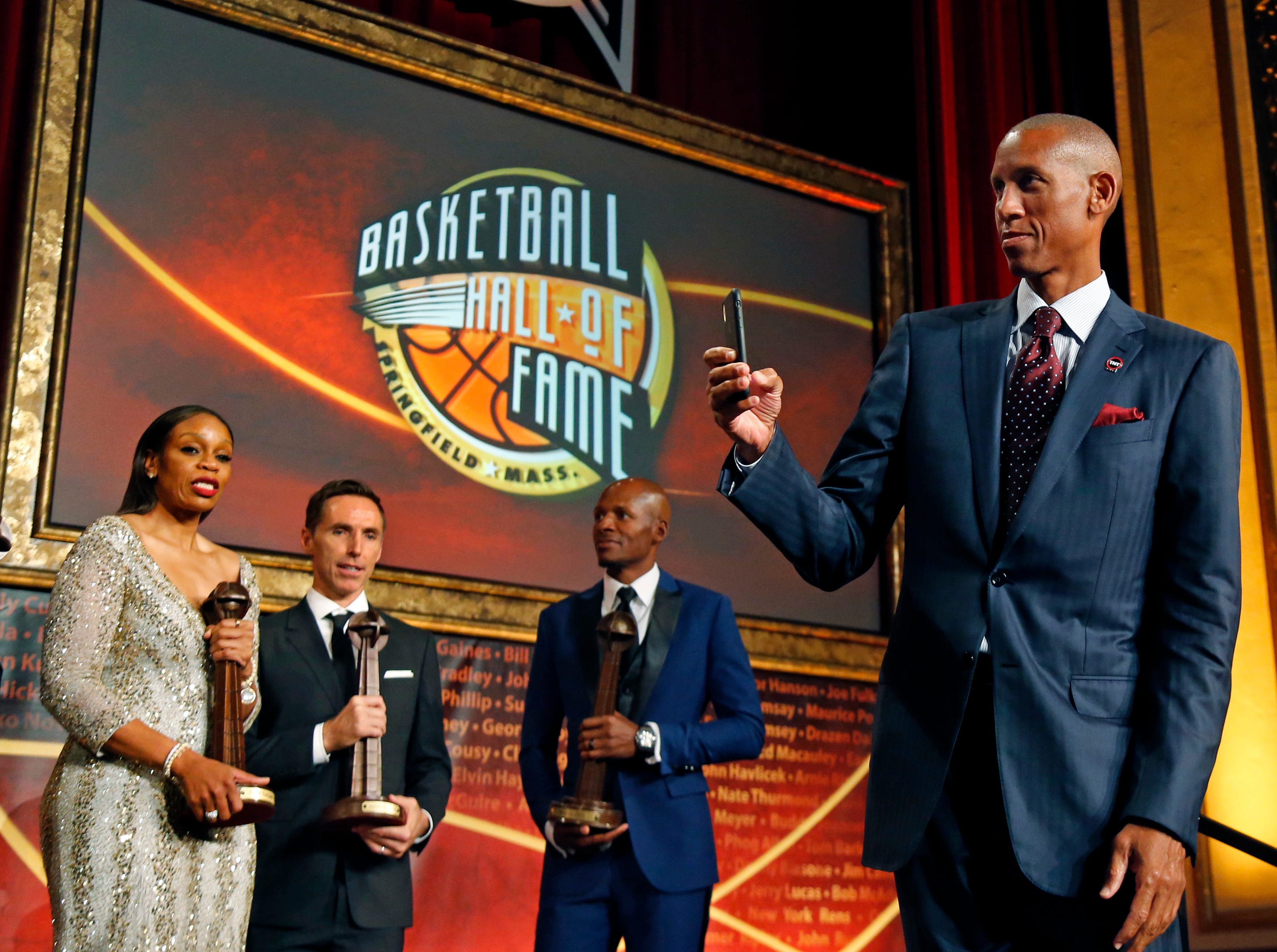 Reggie Miller, right, takes pictures with his phone as 2018 inductees, from left, Tina Thompson, Steve Nash and Ray Allen stand with their trophies after ceremonies at the Basketball Hall of Fame.