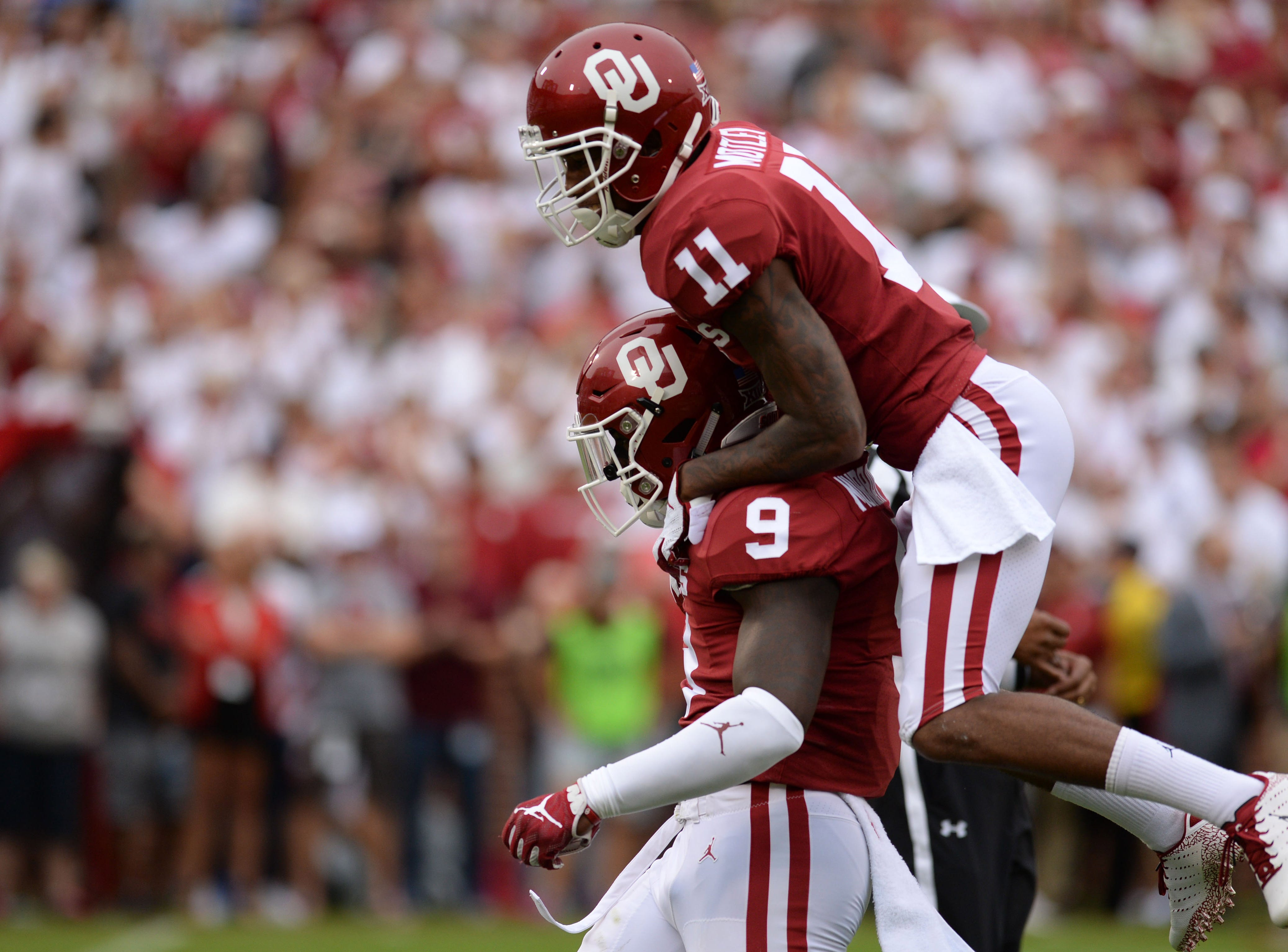 Oklahoma's Kenneth Murray (9) and cornerback Parnell Motley (11) celebrate after a defensive stop against UCLA.
