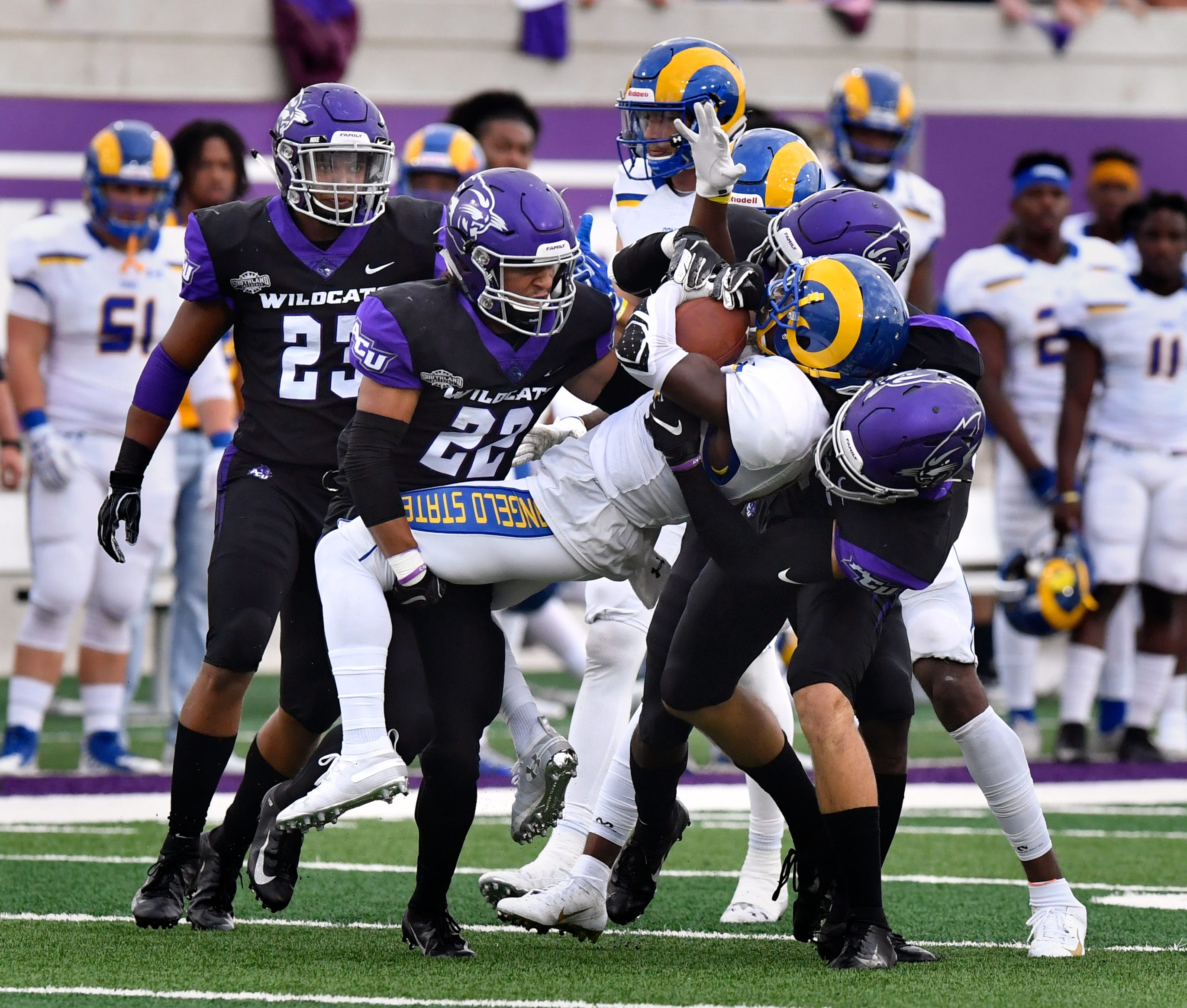 ACU linebacker Jeremiah Chambers (23) looks on as cornerback Koy Richardson (22) and another teammate tackle Angelo State receiver Alize Thomas during a nonconference game Sept. 8 at Wildcat Stadium. ACU won the game 41-24.