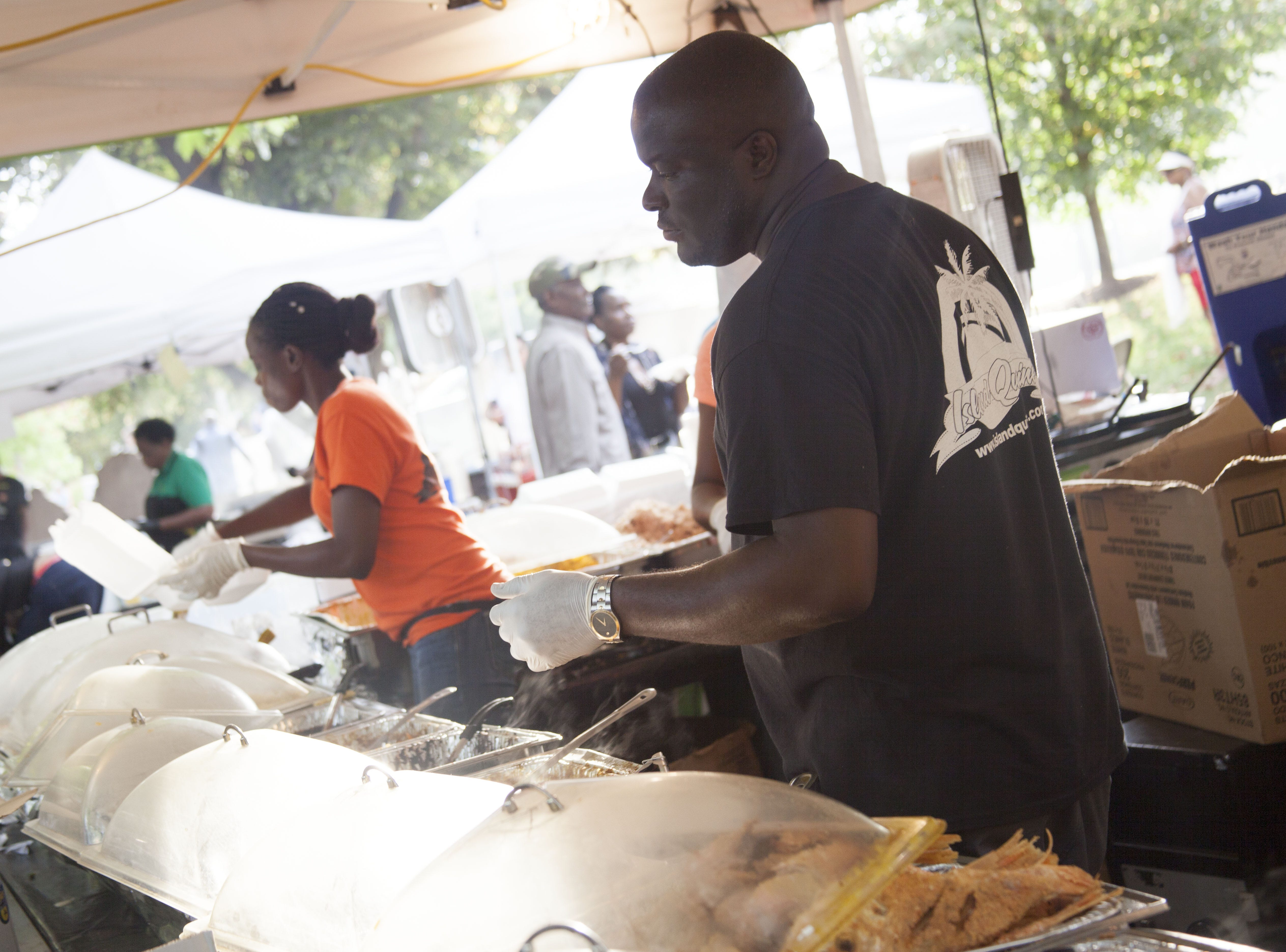 Donovan Murphy of Island Quizine serves Jamaican fare to attendees of the 2018 Goombay Festival at the Roger McGuire Green in Pack Square Park on Sept. 8, 2018.