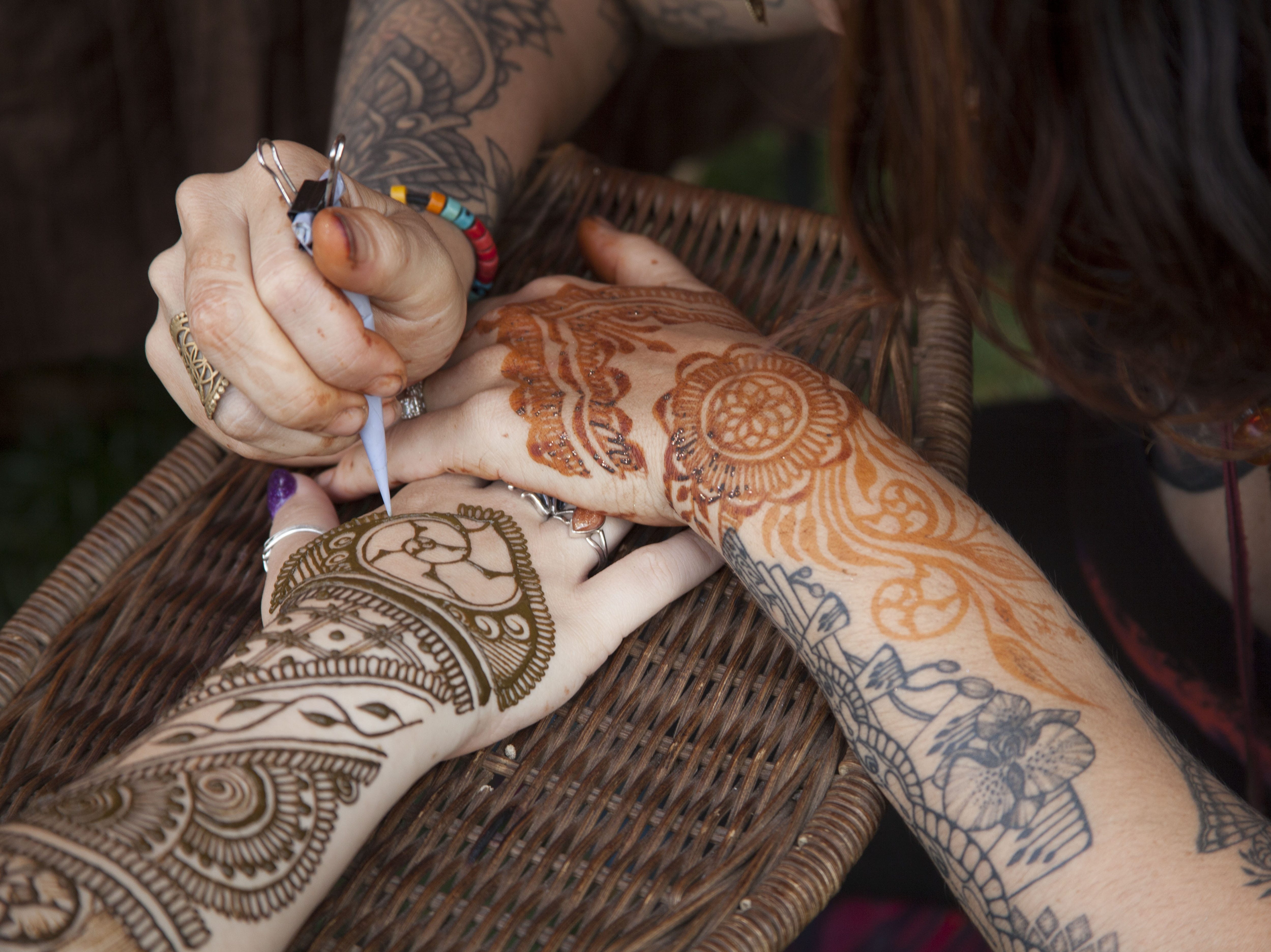River D. creates henna tattoos at the 2018 Goombay Festival at the Roger McGuire Green in Pack Square Park on Sept. 8, 2018.