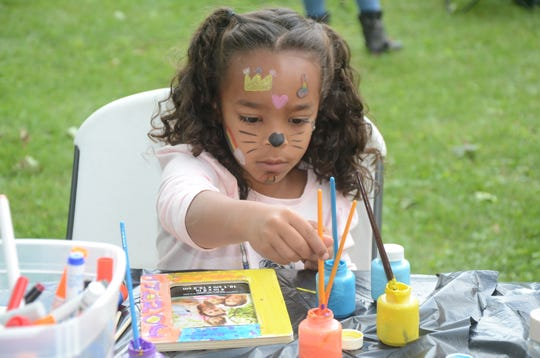 """Johari Rugutt, 5, of Bay City, paints a picture frame Sunday in Marshall during the 40th anniversary of Special Days Camps. Her mother, Jodi Rugutt, 33, a cancer survivor, attended the camp as a 7-year-old. """"You just get to be a kid, not a kid with cancer."""""""