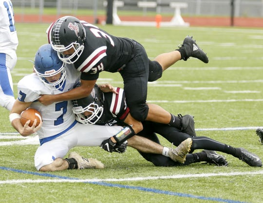 Gavin Elston of Horseheads is brought down by Elmira's Devin Hoskins (34) and Jeff Daugherty during the Express' 40-27 win Sept. 8, 2018 at Ernie Davis Academy.