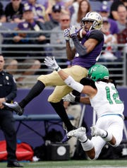 Washington's Quinten Pounds, top, catches the ball in front of North Dakota's Hayden Blubaugh in the first half of an NCAA college football game Saturday, Sept. 8, 2018, in Seattle. (AP Photo/Elaine Thompson)