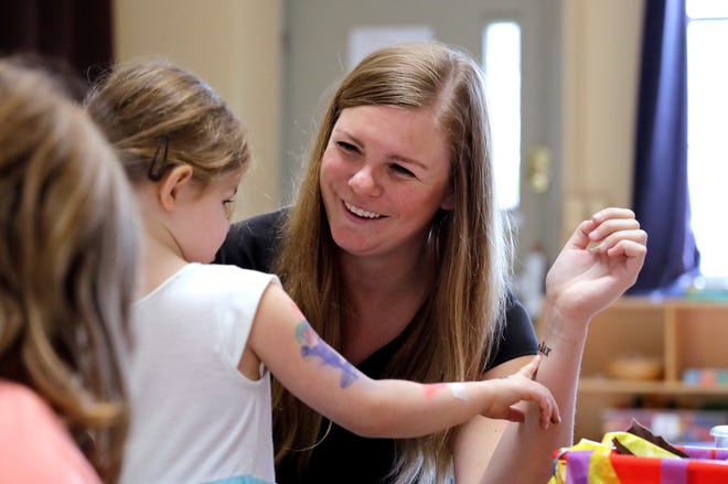 """Director Jenny Cimbalnik talks with a child at the Wallingford Child Care Center in Seattle. A dire workforce crisis in a booming U.S. economy is forcing many in the child care industry to turn to business tactics more closely resembling Wall Street than Sesame Street. Non-compete and """"hold-harmless"""" legal agreements, college tuition incentives for workers and steep waiting-list fees for parents are fast becoming the norm."""