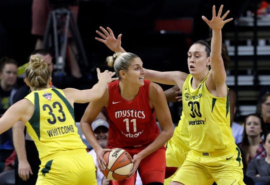 Washington Mystics' Elena Delle Donne (11) looks for room to pass as Seattle Storm's Sami Whitcomb (33) and Breanna Stewart (30) defend.