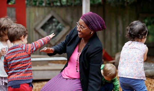"Teacher Fatuma Yusuf interacts with children on the playground at the Wallingford Child Care Center in Seattle. A dire workforce crisis in a booming U.S. economy is forcing many in the child care industry to turn to business tactics more closely resembling Wall Street than Sesame Street. Non-compete and ""hold-harmless"" legal agreements, college tuition incentives for workers and steep waiting-list fees for parents are fast becoming the norm."