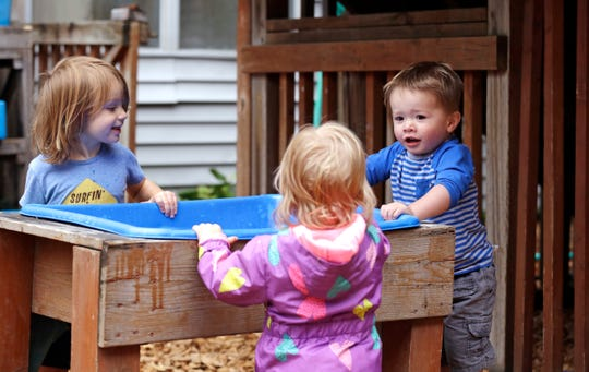 "Astrid Kozlen, left, and Vincent Seeborn, right, talk with another toddler at a splash bin in the playground at the Wallingford Child Care Center in Seattle. A dire workforce crisis in a booming U.S. economy is forcing many in the child care industry to turn to business tactics more closely resembling Wall Street than Sesame Street. Non-compete and ""hold-harmless"" legal agreements, college tuition incentives for workers and steep waiting-list fees for parents are fast becoming the norm."