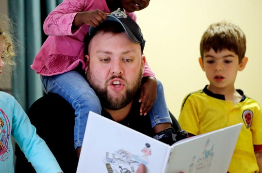 "Teacher Joshua Gielgens reads to Arlo Morgenroth, right, and other children at the Wallingford Child Care Center in Seattle. A dire workforce crisis in a booming U.S. economy is forcing many in the child care industry to turn to business tactics more closely resembling Wall Street than Sesame Street. Non-compete and ""hold-harmless"" legal agreements, college tuition incentives for workers and steep waiting-list fees for parents are fast becoming the norm."