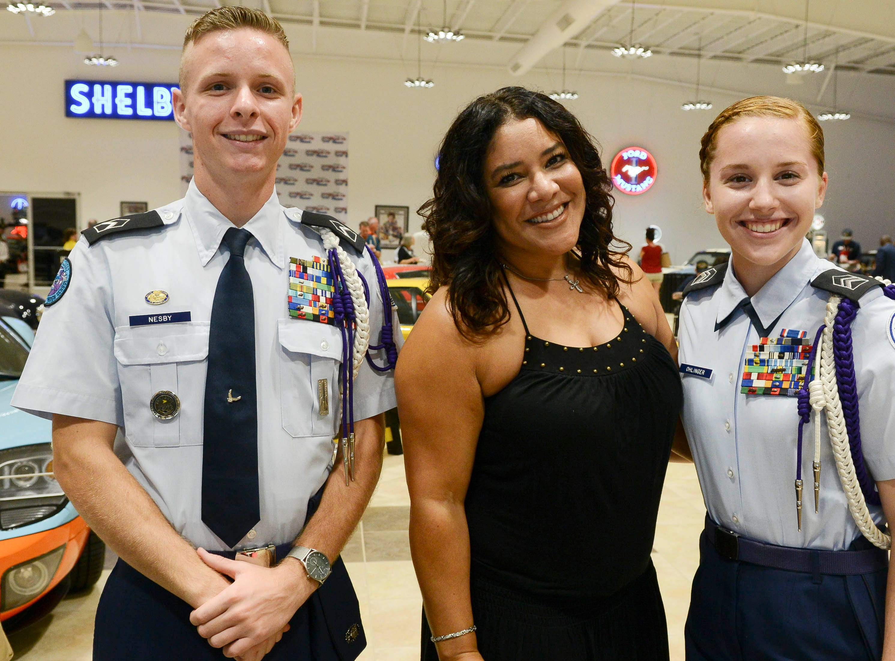 Travis Nesby, Delfina Gomez and Carmen Ohlinger get their picture taken during the Stars and Stripes fundraiser at American Muscle Car Museum. The event was a fundraiser for Space Coast Honor Flight.