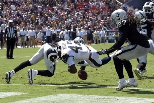 Los Angeles Rams running back John Kelly (42) scores on a 0-yard fumble recovery as Oakland Raiders cornerback Antonio Hamilton (32) and safety Reggie Nelson (27) defend in the second quarter during a preseason game at Los Angeles Memorial Coliseum.