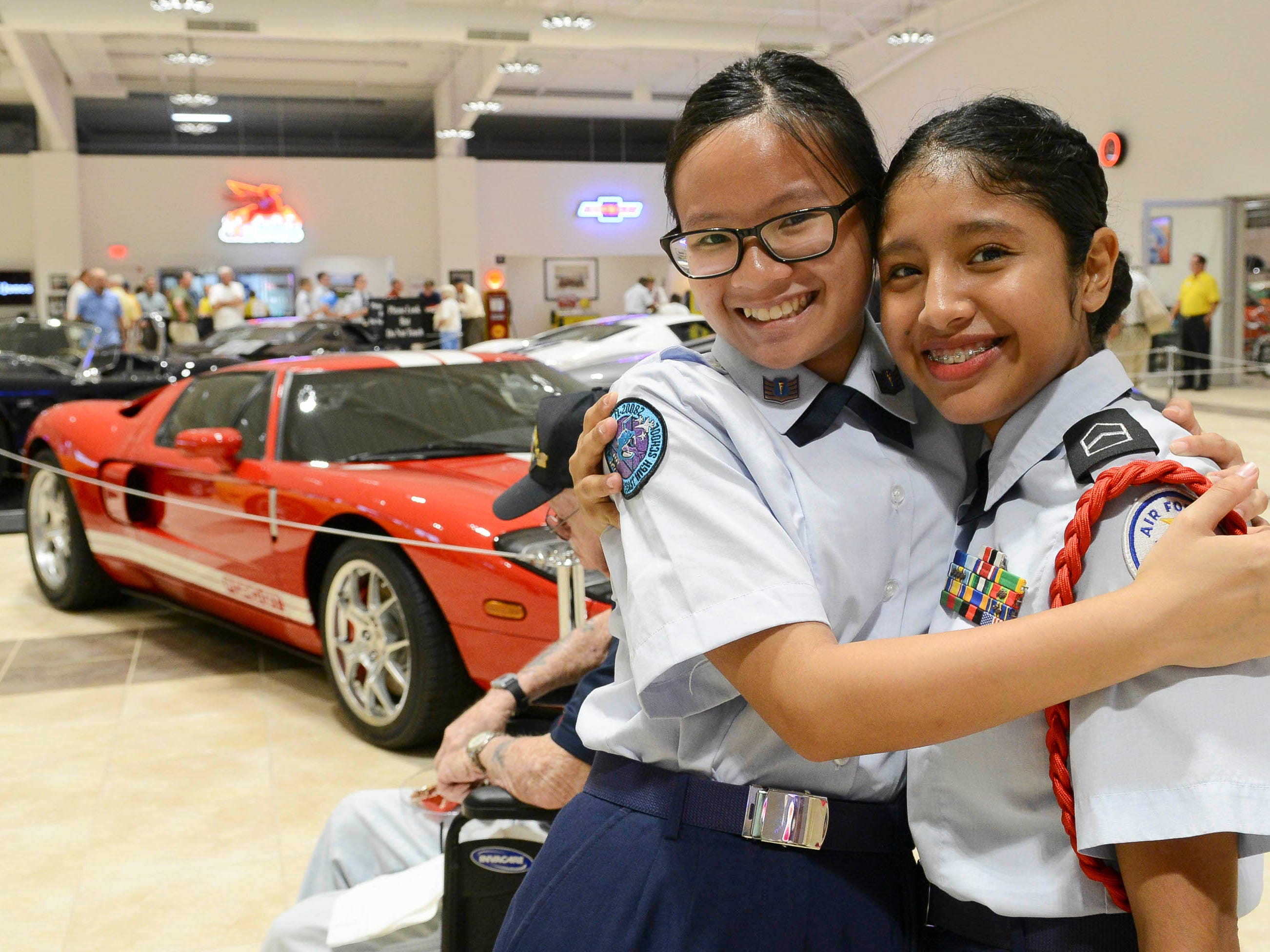 Lisa Nguyen and Madelyne Andrade get their picture taken during the Stars and Stripes fundraiser at American Muscle Car Museum. The event was a fundraiser for Space Coast Honor Flight.