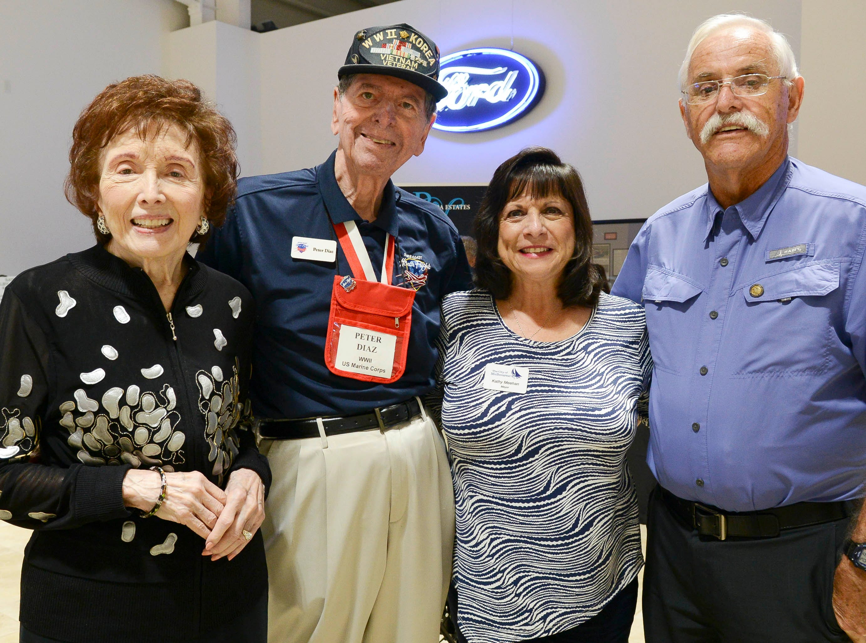 Georgette and Peter Diaz and Kathy and George Meehan get their picture taken during the Stars and Stripes fundraiser at American Muscle Car Museum. The event was a fundraiser for Space Coast Honor Flight.