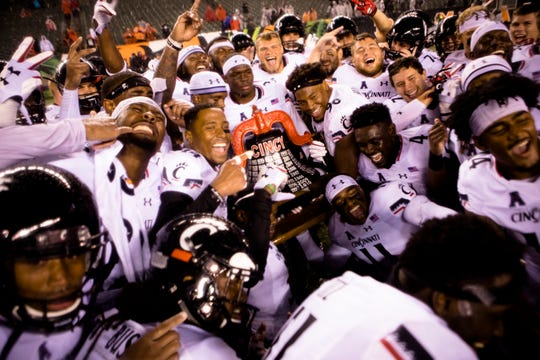 Cincinnati Bearcats pose with the bell after winning the NCAA football game against Miami (Oh) Redhawks 21-0 on Saturday, Sept. 8, 2018, in Downtown Cincinnati.