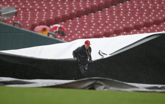 A member of the Cincinnati Reds grounds crew pulls a tarp to cover the field as a rain delay is called during the eighth inning of a baseball game against the San Diego Padres, Sunday, Sept. 9, 2018, in Cincinnati.