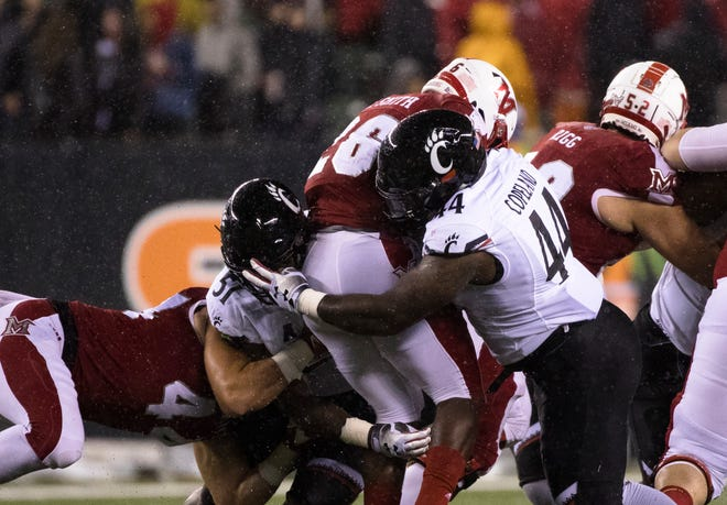 Cincinnati Bearcats defensive end Kimoni Fitz (51) and defensive tackle Marquise Copeland (44) tackle Miami (Oh) Redhawks running back Alonzo Smith (26) during their game in September, won 21-0 by UC