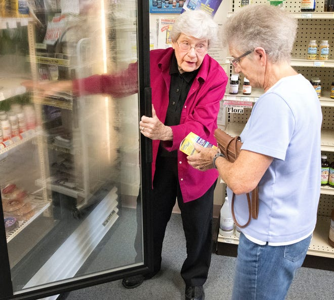 In this Aug. 30, 2018 photo, Marguerite Kuhl, left, helps customer Sharon Juelfs of Holstein, Iowa, at Health Plus in Sioux City, Iowa. Kuhl, 95, retired Aug. 31 after entering the workplace at age 15. She retired once at age 72, then returned to the workforce after getting bored.