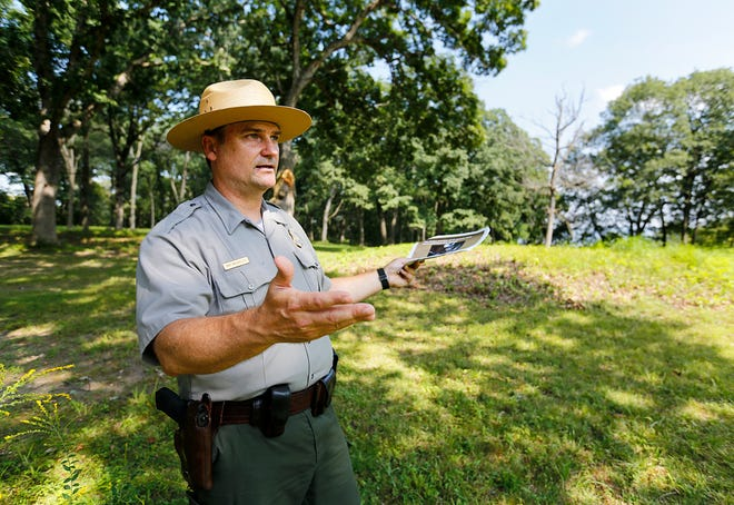 In this Monday, Aug. 27, 2018 photo, David Barland-Liles, lead ranger at Effigy Mounds National Monument, discusses his past investigation to recover stolen human remains while at the site of the Marching Bear Mounds Group in Harpers Ferry, Iowa.
