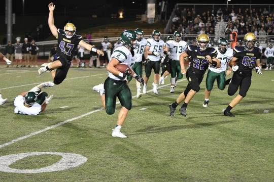 Pella's Aaron Downs (2) evades Norwalk's Nate Heckert (47), Ben Clark (32) and Ethan Stockwell (62) during Pella's 31-17 win at Norwalk on Friday.