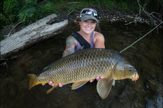 Leah Jones poses for a photo with a carp from the Huron River in 2018.
