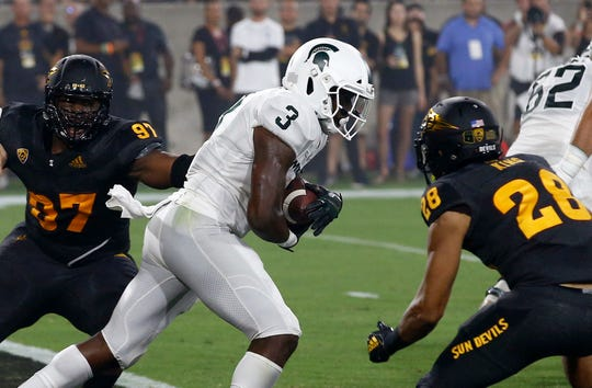 Michigan State running back LJ Scott gets past Arizona State defensive lineman Shannon Forman (97) and defensive back Demonte King (28) during the first half Saturday, Sept. 8, 2018, in Tempe, Ariz.