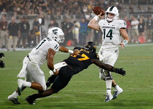 Michigan State quarterback Brian Lewerke passes as he is pressured by Arizona State linebacker Darien Butler. Running back Connor Heyward tries to make the block during the first half Saturday, Sept. 8, 2018, in Tempe, Ariz.