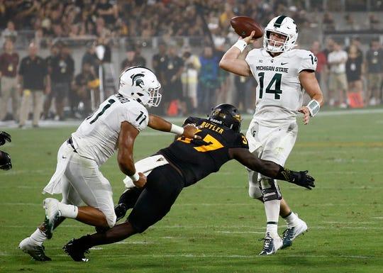 Michigan State quarterback Brian Lewerke passes as he is pressured by Arizona State linebacker Darien Butler. Running back Connor Heyward tries to make the block during the first half Saturday, Sept. 8, 2018, in Tempe, Ariz.