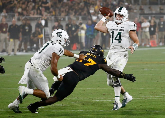 Michigan State quarterback Brian Lewerke passes as he is pressured by Arizona State linebacker Darien Butler.