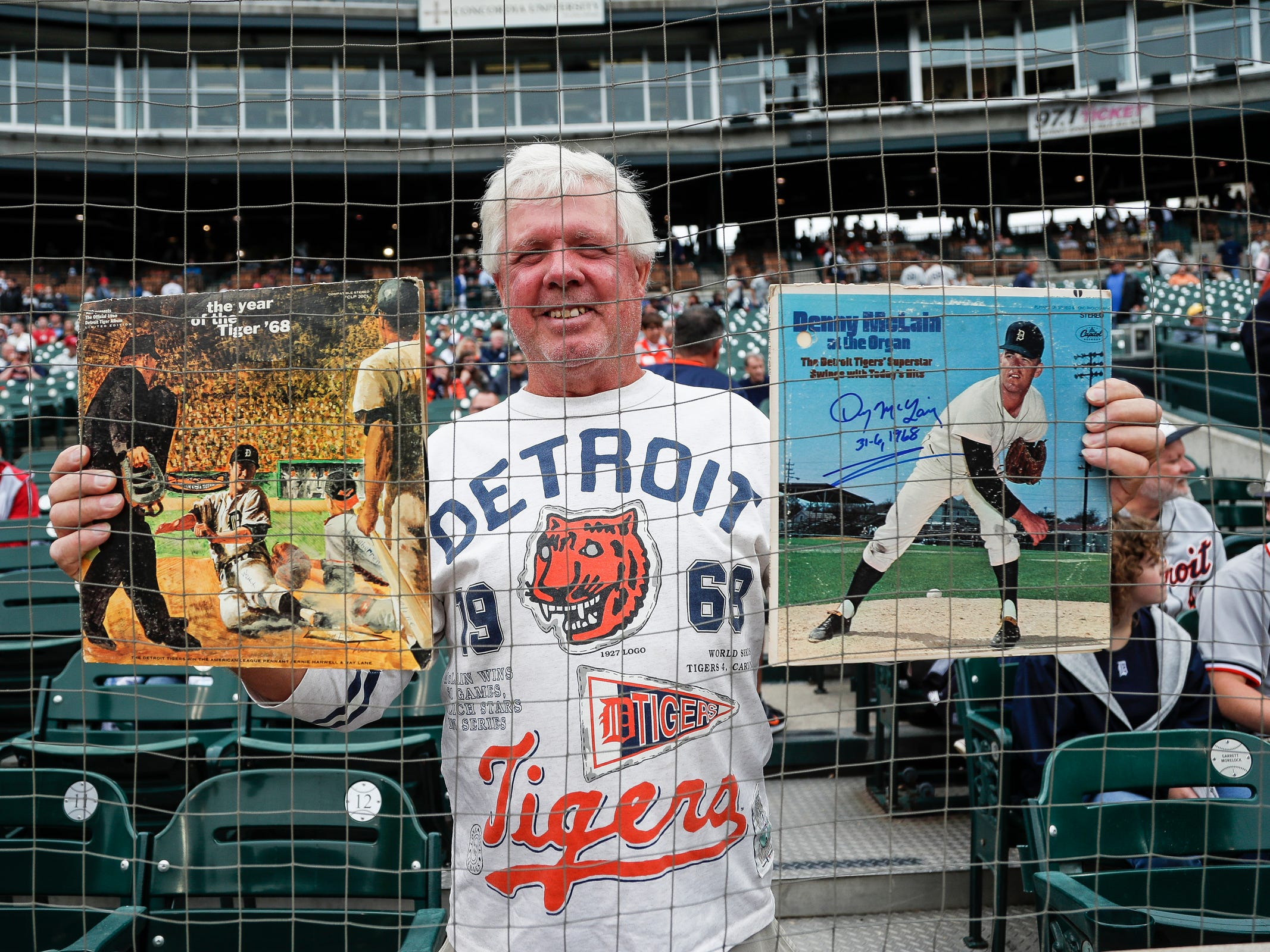 Marion Kim of Beach City, Ohio, poses for a photo with two old Detroit Tigers records during the celebration of the 50th anniversary of the 1968 World Series championship at Comerica Park in Detroit, Saturday, Sept. 8, 2018.